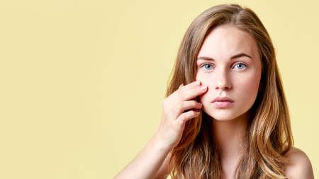 Junger Rothaarigejugendlicher mit Selbst gibt das Untersuchen des Spiegels heraus. Mädchen mit niedrigem Selbstwertgefühl ihre Haut in einem Spiegel überprüfend.