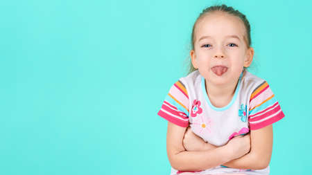 Adorable little girl with crossed arms sticking her tongue out. Cheeky preschooler waist up portrait on pastel coloured candy blue background. Reklamní fotografie