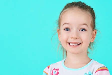 Entzückendes kleines Mädchen, das ihren ersten verlorenen Milchzahn lächelt und vorführt. Nettes Vorschülerporträt, nachdem ihr vorderer Milchzahn fallen gelassen worden ist.