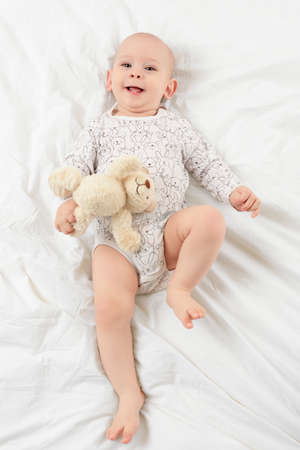 Adorable smiling baby boy with blue eyes lying on a bed with his favorite stuffed teddy bear toy, looking at camera. Cute toddler in pajamas full body portrait. Foto de archivo