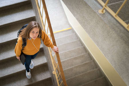 Young depressed lonely female college student walking down the stairs at her school, looking up at the camera. Education, Bullying, Depression concept. 版權商用圖片