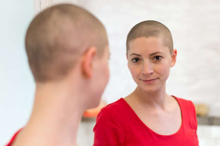 Young adult female cancer patient looking in the mirror, smiling, happy about her new short hair. Reklamní fotografie - 98045359