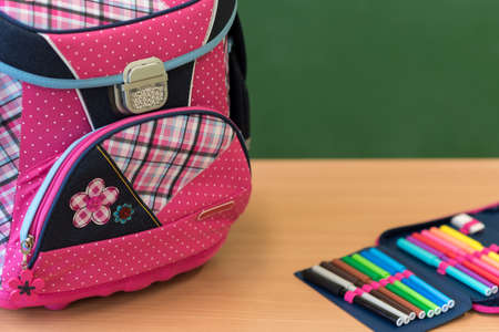 Pink girly school bag and pencil case on a desk against greenboard. First day of school concept.
