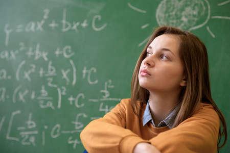Chica adolescente en clase de matemáticas abrumado por la fórmula matemática. Presión, educación, concepto de éxito.