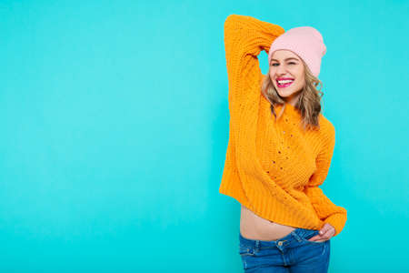 Crazy beautiful trendy girl with cheeky smile in colorful clothes and pink beanie hat. Attractive cool young woman portrait over pastel blue background.