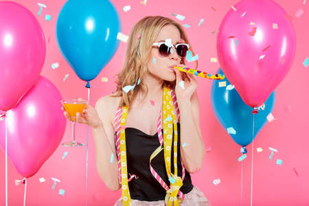 Gorgeous trendy young woman in party outfit celebrating birthday. Party mood, balloons, flying confetti, cocktail and dancing concept on pastel pink background.