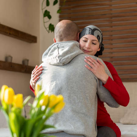 Young adult female cancer patient hugging her husband at home after treatment in hospital. Cancer and family support concept.