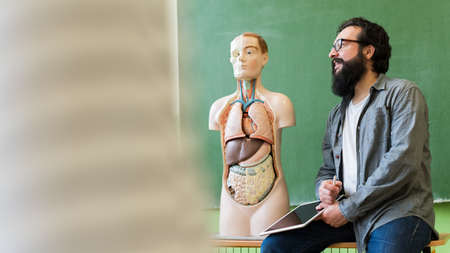 Young male hispanic teacher in biology class, holding digital tablet and teaching human body anatomy, using artificial body model to explain internal organs. Stock Photo