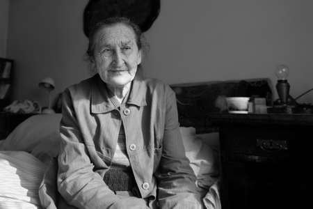 Beautiful 80 plus year old senior woman portrait. Black and white image of elderly worried woman sitting on a bed in a nursing home.