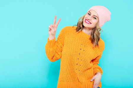 Crazy beautiful trendy girl in mustard coloured sweater and pink beanie hat making peace sign hand gesture. Attractive cool young smiling woman portrait over pastel blue background.