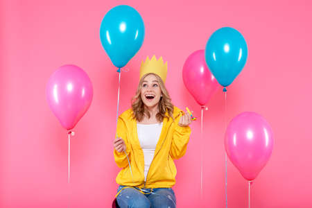 Funny girl in birthday hat, balloons and blowout horn on pastel pink background. Attractive trendy teenager celebrating birthday.