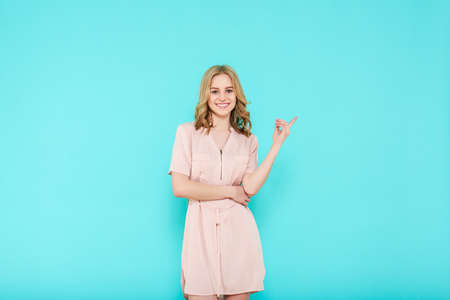Trendy attractive young woman wearing elegant summer dress posing over pastel blue background. Front view of smiling woman pointing with finger to the side and looking at camera.