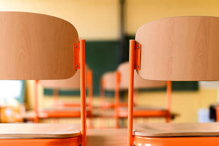 Empty classroom with school desks, chairs and blackboard. Education concept.
