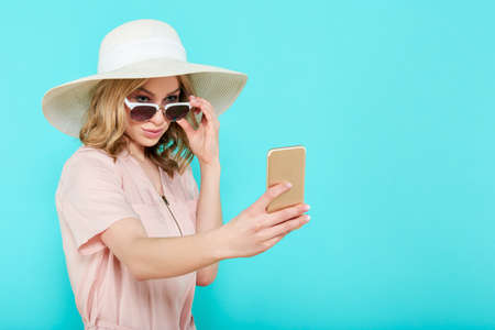 Beautiful young woman in elegant pale pink dress, sunglasses and summer hat taking selfie. Studio portrait of fashionable woman. Summer Vacation concept. Stock Photo