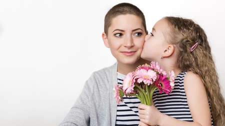 Happy Mother's Day, Women's day or Birthday background. Cute little girl giving mom, cancer survivor,  bouquet of pink gerbera daisies. Loving mother and daughter. Stock Photo