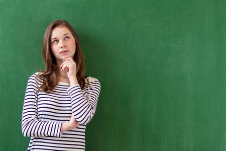 Student thinking and leaning against green chalkboard background. Pensive girl looking up. Caucasian female student portrait with copy space. Imagination, ideas, future, possibilities concept.