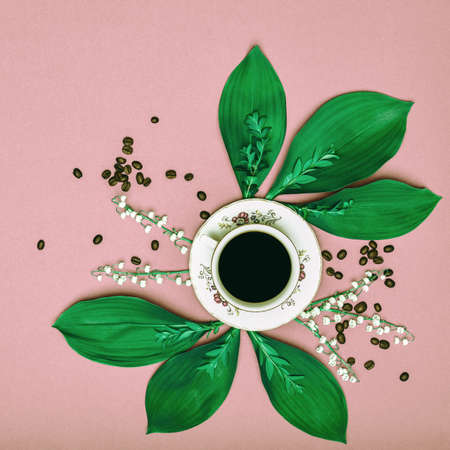 Cup of black coffee with flowers on pink coloured art background. Good Morning coffee floral setup concept. Stock Photo