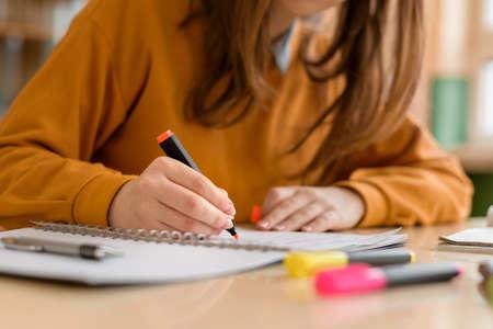 Jeune étudiante méconnaissable en classe, prenant des notes et utilisant un surligneur. Étudiant ciblé en classe. Concept d'éducation authentique.