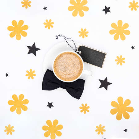 Happy Father's Day Background. Cup of coffee and black bow tie on white background flat lay. Floral Fathers day still life setup.