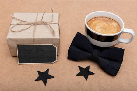 Happy Father's Day Background. Cup of coffee, beautiful present and black bow tie on brown background flat lay. Fathers day still life setup.
