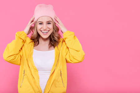Beautiful hipster teenage girl in bright yellow jacket and pink beanie hat super excited. Attractive cool young woman fashion portrait over pastel pink background.