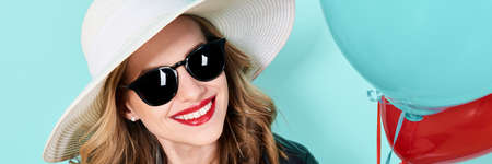 Beautiful woman in summer hat and sunglasses holding balloons. Attractive cool young woman fashion portrait over pastel blue banner background. Reklamní fotografie
