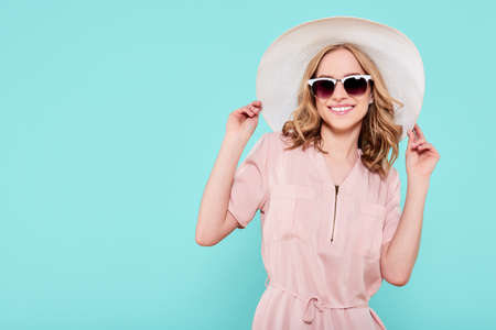 Elegant young attractive woman wearing pale pink summer dress, straw hat and sunglasses, thinking about her summer vacation, isolated over pastel blue background.