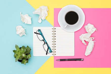 Writers block. Ideas, brainstorming, creativity, imagination, deadline, frustration concept. Top view photo of office desk with blank mock up open notepad and crumpled paper on pastel background. Stock Photo
