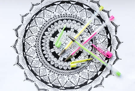 Adult coloring book, new stress relieving trend. Art therapy, mental health, creativity and mindfulness concept. Adult coloring page with pastel colored gel pens, Flat lay background. Stock Photo