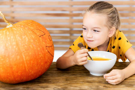 Cute little girl eating pumpkin soup and looking at a large Halloween pumpkin, with vicious face expression. Halloween conceptual background.