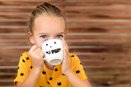 Cute little girl drinking pumpkin soup out of a cup with Halloween anthropomorphic smiley face. Halloween lifestyle conceptual background.