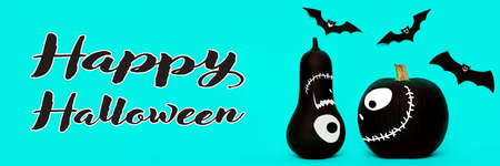 Cute Halloween pumpkins with funny smiling faces looking at each other and paper bats flying over pastel blue background. Halloween concept banner.