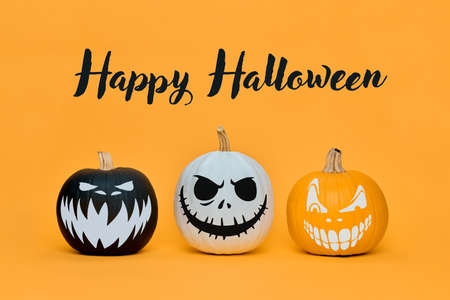 Three Spooky Halloween pumpkins with scary face expressions over orange background. Halloween concept. Stock Photo
