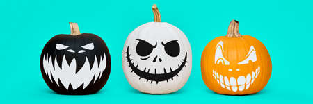 Three Spooky Halloween pumpkins with scary face expressions over pastel blue background. Halloween concept banner.