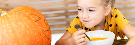 Cute little girl eating pumpkin soup and looking at a large Halloween pumpkin, with vicious face expression. Halloween conceptual banner.