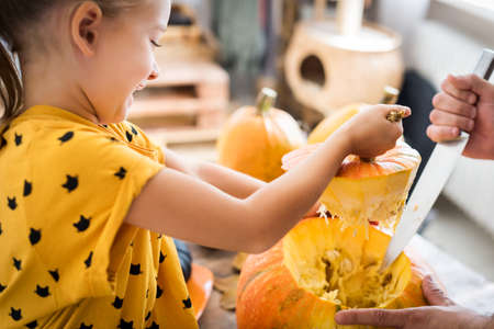 Cute little girl sitting on kitchen table, helping her father to carve large pumpkin, smiling. Halloween family lifestyle background.