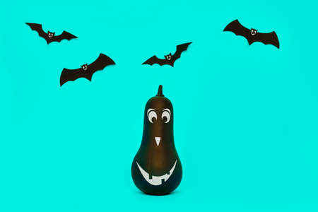 Cute Halloween pumpkin with funny smiling face and paper bats flying over pastel blue background. Halloween concept.