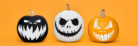Three Spooky Halloween pumpkins with scary face expressions over orange background. Halloween concept banner. Stock Photo