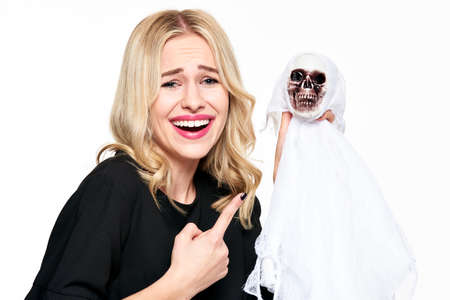 Gorgeous young woman in witch costume holding Halloween skeleton decoration laughing and pointing a finger at it. Halloween concept over white background. Banque d'images