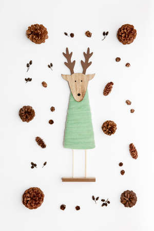 Cute reindeer chrismas decoration flat on white background. Xmas composition with pine cones and a reindeer toy. Stock Photo