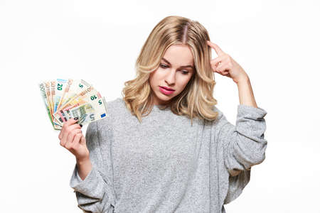 Pretty young woman in grey sweater holding bunch of Euro banknotes, scratching her head thinking, isolated on white background. Stock Photo