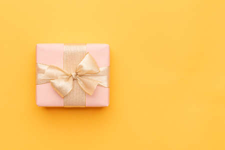 Christmas background. Beautiful christmas gift isolated on bright yellow background. Pink xmas box. Gift wrapping concept.