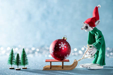 Cute Cheerful Santas Helper Elf Pulling Santas Sleigh With Christmas Bauble.North Pole Christmas Scene. Santas Workshop. Elf at work. Stock Photo