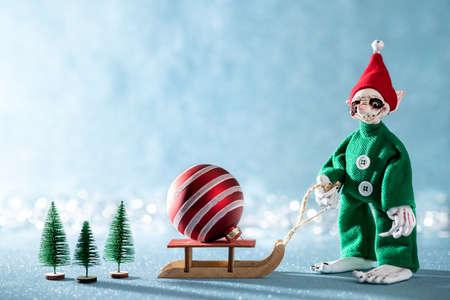 Cute Cheerful Santas Helper Elf Pulling Santas Sleigh With Christmas Bauble.North Pole Christmas Scene. Santas Workshop. Elf at work. Stock Photo