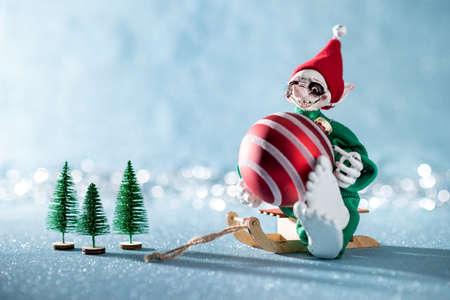 Cute Cheerful Santas Helper Elf Sitting on Santas Sleigh With Christmas Bauble. North Pole Christmas Scene. Santas Workshop. Elf at work. Stock Photo