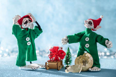 Worried Santas Helper Elf With Head in Hands Standing Next to Another Elf That Broke a Christmas Bauble. North Pole Christmas Scene. Santas Workshop. Elves at work. Stock Photo