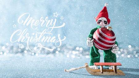 Cute Cheerful Santas Helper Elf Loading Christmas Bauble Onto Santas Sleigh. North Pole Christmas Scene. Santas Workshop. Elf at work.