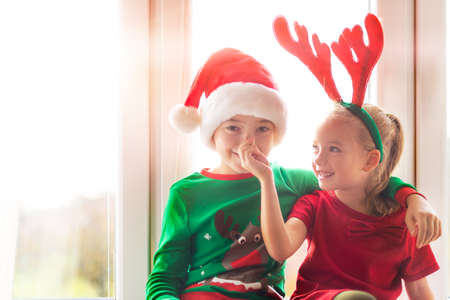 Brother and sister sitting on window sill at christmas time, having fun together. Christmas family time lifestyle.