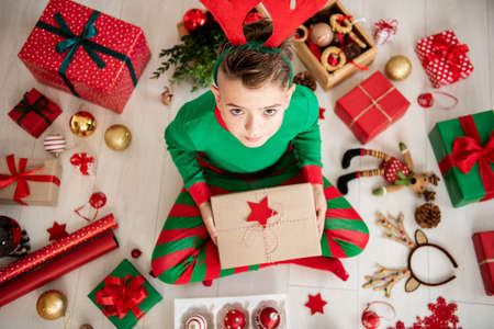 Curious young boy wearing xmas pajamas sitting on the floor, opening his christmas present, top view. Stock Photo