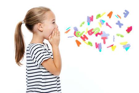 Schattig klein meisje in gestript T-shirt dat Alfabetletters schreeuwt. Logopedie concept op witte achtergrond. Stockfoto